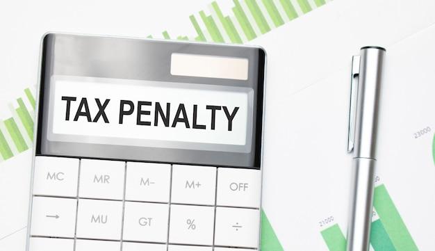 Concetto di affari e finanza. sul tavolo c'è una penna e una calcolatrice su cui è scritto il testo - sanzione fiscale