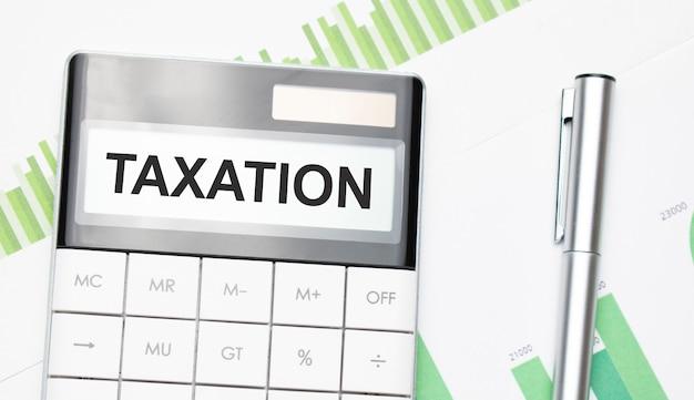 Concetto di affari e finanza. sul tavolo c'è una penna e una calcolatrice su cui è scritto tassazione