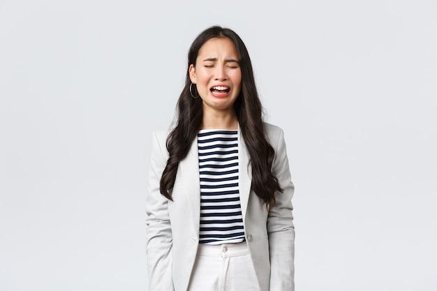 Affari, finanza e occupazione, concetto di imprenditrici di successo. signora dell'ufficio asiatica inquieta e in difficoltà che si sente triste, piange e singhiozza, in piedi depressa su sfondo bianco.