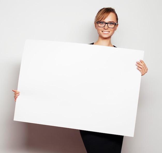 Concetto di affari, finanza e persone: ritratto di una bella donna d'affari in possesso di un cartellone bianco. pronto per aggiungere testo. su sfondo grigio.