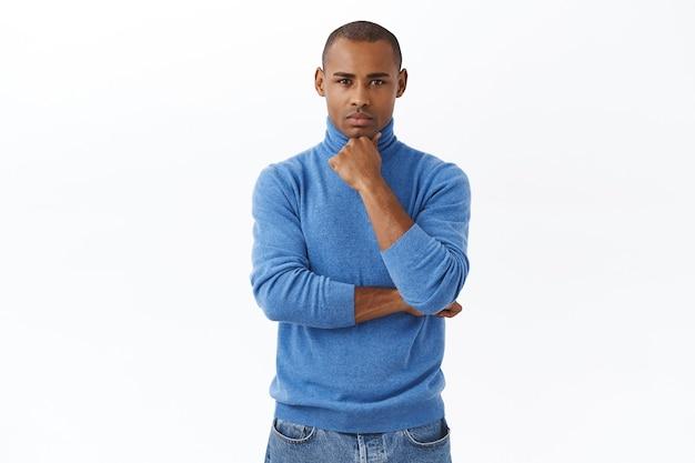 Concetto di affari, finanza e persone. uomo afroamericano dall'aspetto serio che ascolta notizie importanti, accigliato e tocca il mento