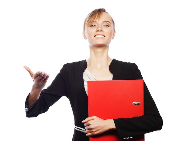 Concetto di affari, finanza e persone: giovane donna d'affari che tiene cartelle e mostra qualcosa, su sfondo bianco