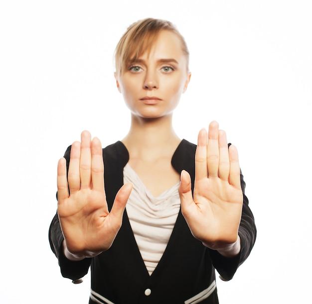 Concetto di affari, finanza e persone: giovane donna d'affari che fa desture di arresto. isolato su sfondo bianco.