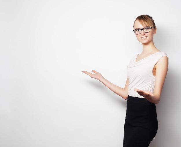 Concetto di affari, finanza e persone. giovane donna d'affari mostra qualcosa, su grigio