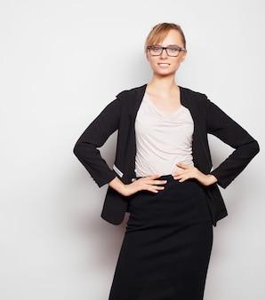Concetto di affari, finanza e persone: giovane donna d'affari con gli occhiali. su sfondo grigio.