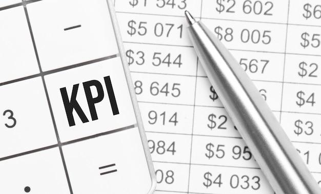 Affari e finanza. sul tavolo c'è un rapporto, una penna e una calcolatrice, sul cui tasto grande è scritto kpi