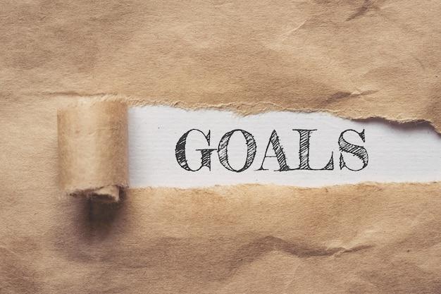 Affari e finanza. carta marrone strappata su uno sfondo bianco, il testo - obiettivi