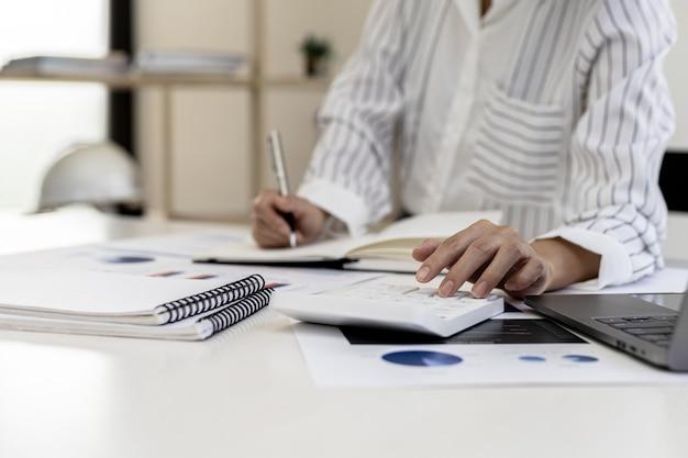 Una donna delle finanze aziendali sta esaminando i documenti finanziari di un'azienda preparati dal dipartimento delle finanze per un incontro con i partner commerciali. concetto di convalida dell'accuratezza dei numeri finanziari.