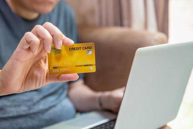 Concetto di affari, finanziario, pagamento e tecnologia. uomo asiatico che tiene e mostra la carta di credito fake mockup e usa il computer portatile.
