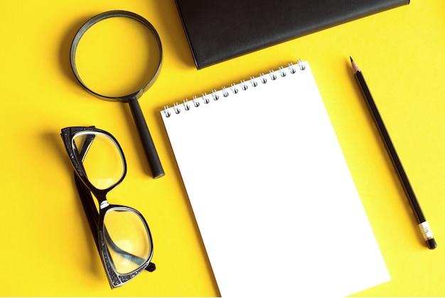 Concetto di affari e finanse con taccuino, lente d'ingrandimento, penna e occhiali neri