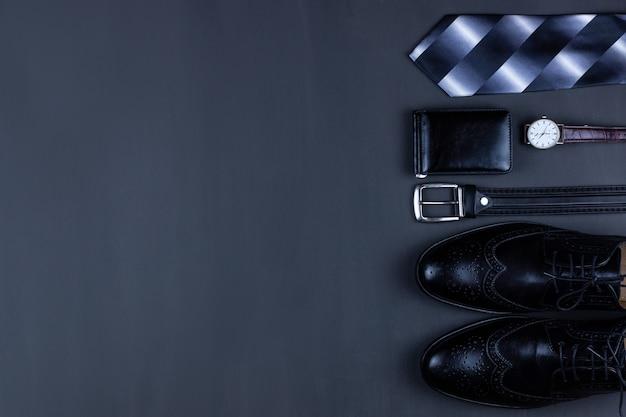 Sfondo piatto aziendale laici con uno spazio di copia. scarpe maschili, portafoglio orologio da polso, cintura, telefono cellulare e una cravatta su sfondo nero.