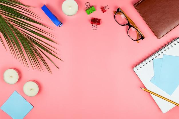 Flatlay aziendale con occhiali, foglia di palma, candele, pinzatrice, penna, quaderno, tosatrice colorata e note di carta. concetto di posto di lavoro di una donna. disteso. sfondo rosa. copyspace