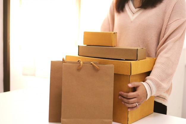 Donna di affari da casa che prepara la scatola di consegna del pacchetto spedizione per lo shopping online. giovani avviare piccoli imprenditori a casa acquisti online