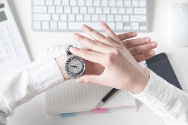 Ragazza di affari che ripara il suo orologio da polso.