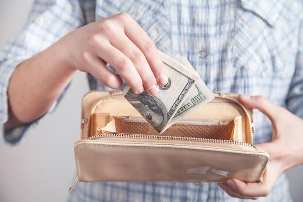 Ragazza di affari che mostra soldi con il portafoglio.