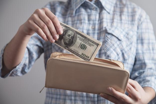 Ragazza di affari che mostra soldi con il portafoglio
