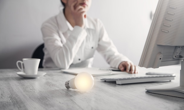 Ragazza di affari che si siede nell'ufficio. lampadina nella scrivania in ufficio. posto di lavoro in ufficio. affari, idea