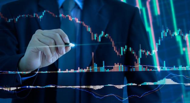 Grafico commerciale e grafico del mercato azionario o del forex trading con investimenti finanziari. uomo d'affari che tiene la penna che tocca su uno schermo virtuale.
