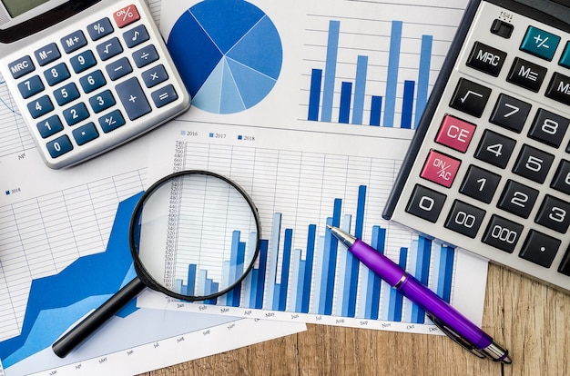 Grafico commerciale con lente d'ingrandimento e penna calcolatrice sul tavolo
