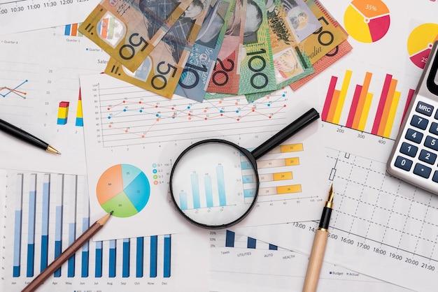 Grafici commerciali con dollari australiani, lente d'ingrandimento, penna e calcolatrice