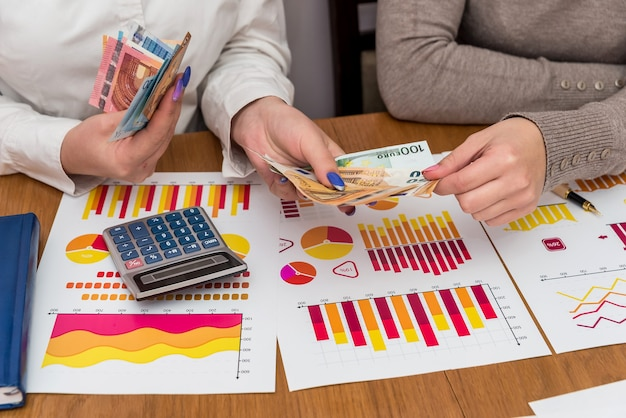 Grafici commerciali con mani femminili che tengono euro