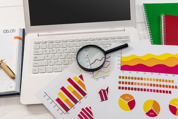 Grafici commerciali con laptop e lente d'ingrandimento alla scrivania
