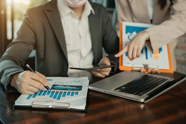 Gruppo aziendale di consulenti finanziari seduti al tavolo e ascoltando il loro manager durante una riunione in ufficio al mattino.