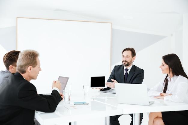Gruppo di lavoro seduto al tavolo in sala conferenze con scrivania