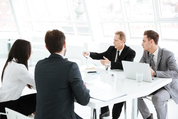 Gruppo di lavoro seduto al tavolo in sala conferenze con laptop