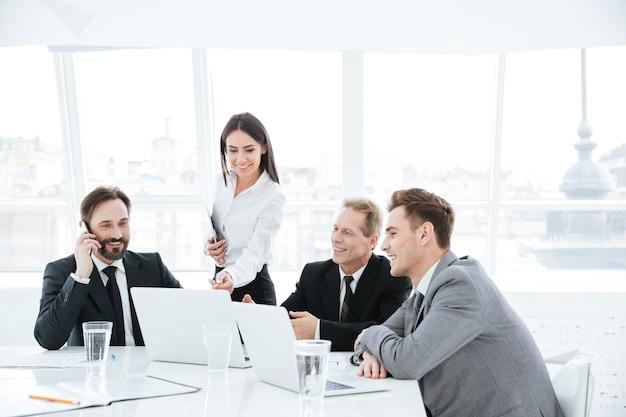 Gruppo di lavoro seduto al tavolo vicino alla finestra nella sala conferenze