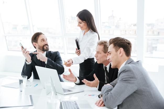 Gruppo di affari seduto al tavolo vicino alla finestra. donna in piedi vicino al tavolo e discute con un uomo che tiene in mano il telefono