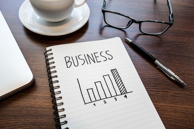 Idee di concetto in crescita di affari con il grafico sul blocco note