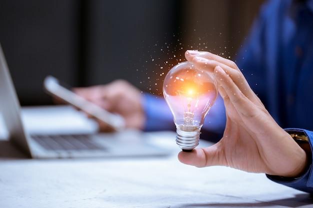 La mano di affari che tiene la lampadina, con l'icona del cervello, la creatività e l'innovazione sono le chiavi del successo, delle nuove idee e del concetto di innovazione.