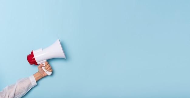 Business hand tiene un megafono da un buco nel muro su sfondo blu. assunzione, pubblicità, pubblicità e concetto di banner.