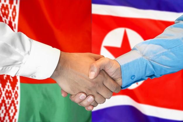 Stretta di mano di affari sullo sfondo di due bandiere.
