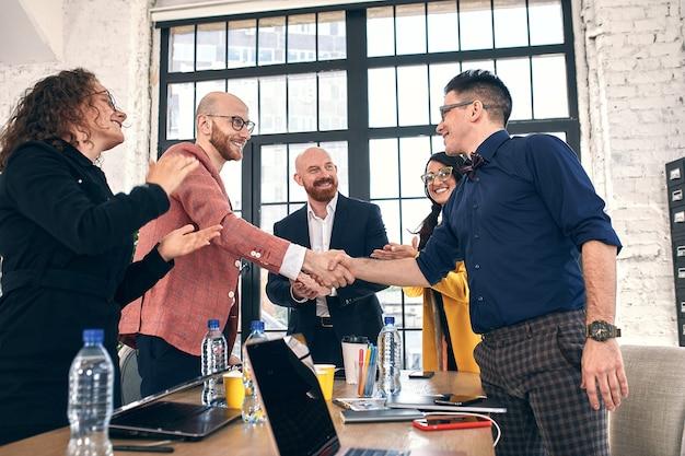 Stretta di mano di affari alla riunione o alla negoziazione in ufficio