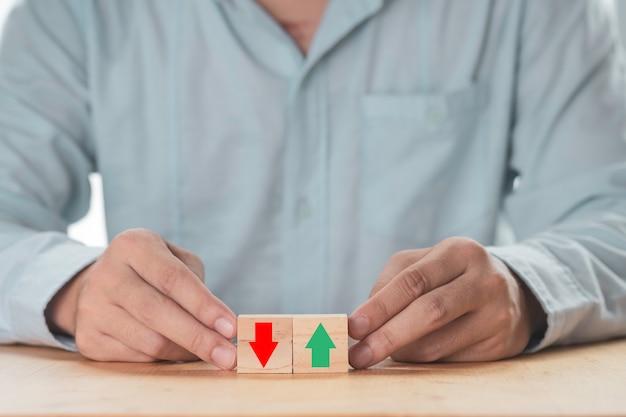 Attività in aumento o in diminuzione, uomo d'affari che tiene freccia su verde o freccia giù rossa che stampa lo schermo sul blocco cubo di legno.