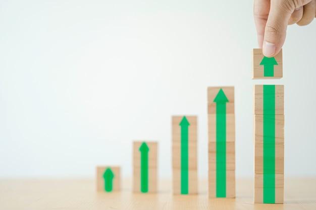 Concetto di crescita degli investimenti aziendali, uomo d'affari che tiene blocco cubo di legno che stampa lo schermo verso l'alto e aumenta la freccia verde.