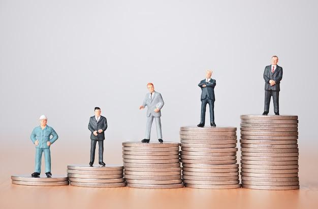 Investimento aziendale e concetto di piallatura. figura in miniatura dell'uomo d'affari che si leva in piedi sull'impilamento delle monete.
