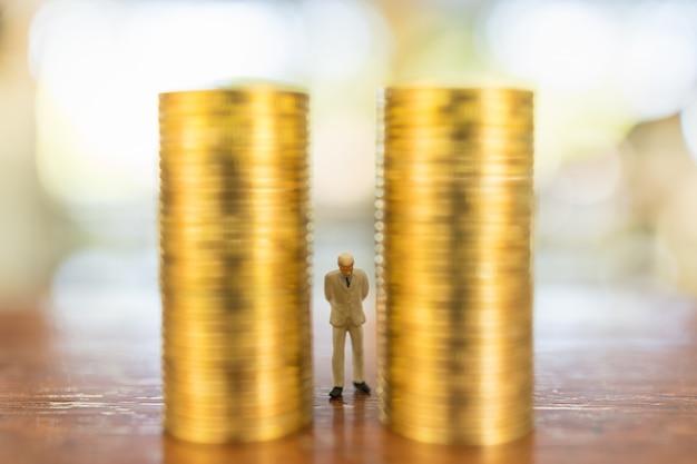 Concetto di affari, investimenti e pianificazione. chiuda su della figura miniatura della gente dell'uomo d'affari che sta fra la pila di monete di oro sulla tavola di legno.