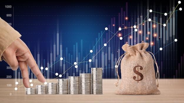 Investimento aziendale e crescita del risparmio per il concetto di pubblicità. impilabile mano dell'uomo d'affari moneta che cresce con grafico grafico di crescita e borsa di denaro sul tavolo di legno, significato di guadagno o tasse