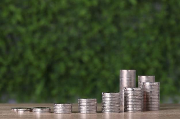 Investimento aziendale e crescita del risparmio per il concetto di pubblicità. impilamento di monete che crescono su un tavolo di legno e sfondo verde della natura, significato di tasse o guadagno di denaro