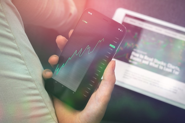 Investimenti aziendali, trading di dati di borsa e grafici di trading con il telefono cellulare a casa. sfondo del concetto di analisi forex e broker, foto a doppia esposizione