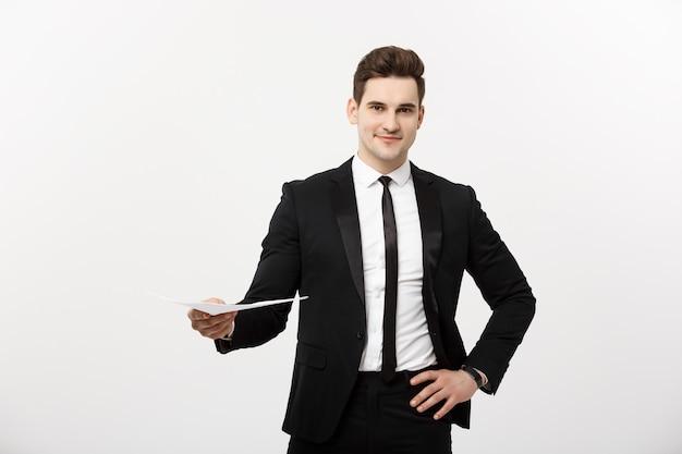Concetto di affari e lavoro: uomo elegante in tuta che tiene in mano un curriculum per l'assunzione di lavoro nell'interno bianco brillante.