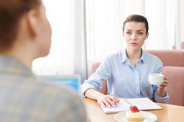 Signore di affari che si siedono al tavolo nel ristorante e discutono di affari davanti a una tazza di caffè: donna attraente ascoltando l'offerta di colleghi