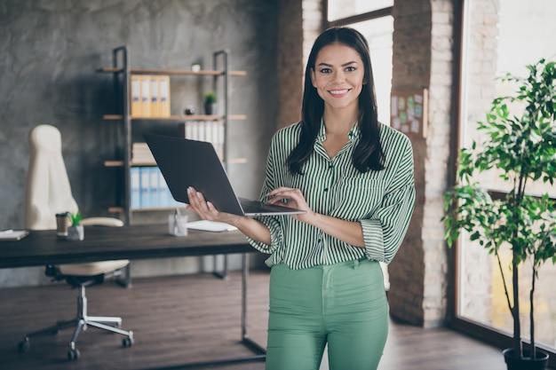 Donna d'affari in chat sul computer portatile in ufficio al chiuso