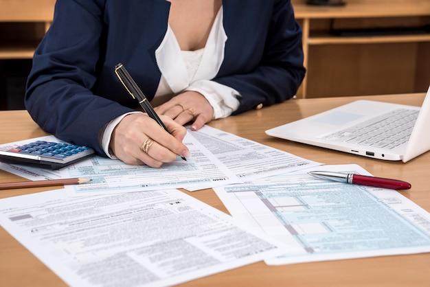 La signora d'affari compila il modulo fiscale 1040