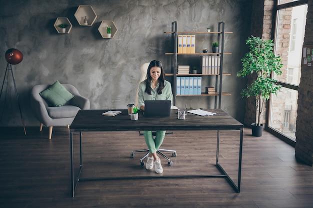 La signora di affari si siede la tabella allo sguardo dell'ufficio nello schermo del laptop