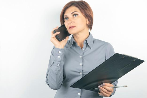 Signora di affari con telefono e documenti in mano sul muro bianco.