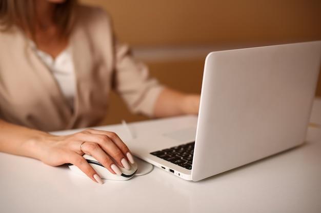 La donna della signora di affari in vestito convenzionale beige lavora al primo piano del mouse e della mano del computer su un'immagine sfocata di una donna